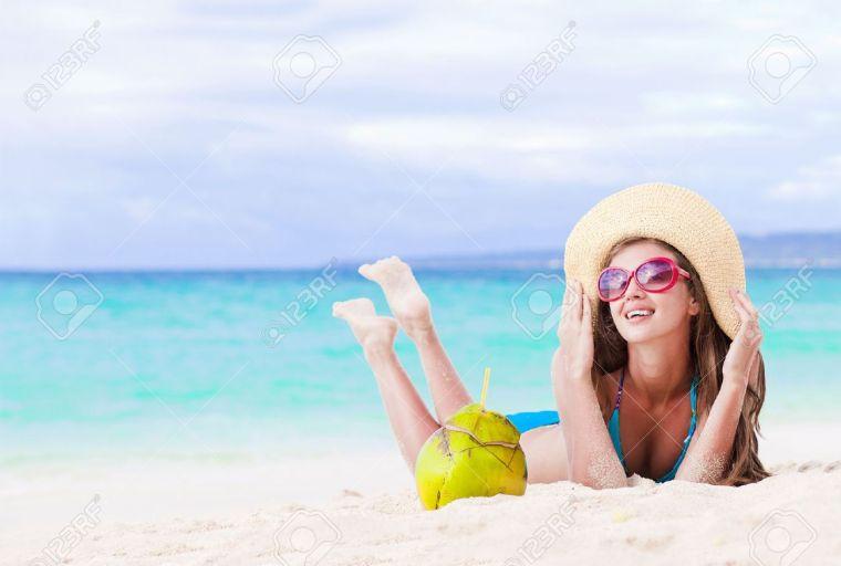 femme avec chapeau de plage en paille à la plage