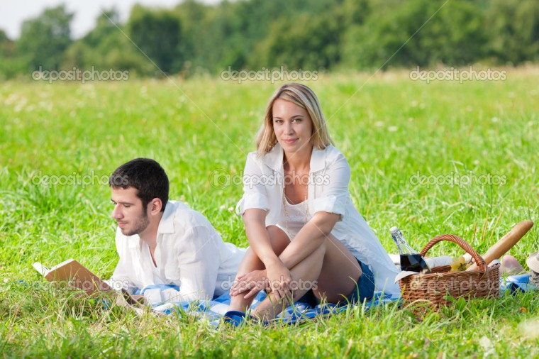 Picnic - Romantic happy couple in meadows nature reading book